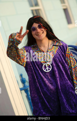 A man giving peace sign dressed up as a hippy for a 1970's decade themed birthday party, UK - Stock Photo