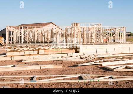 Building materials are stacked on the construction site for a new wood frame house being built in Arizona. - Stock Photo