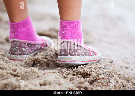 Colorful shoes of a little girl on summer vacation, standing on a Lake Winnipeg beach.  Manitoba, Canada. - Stock Photo