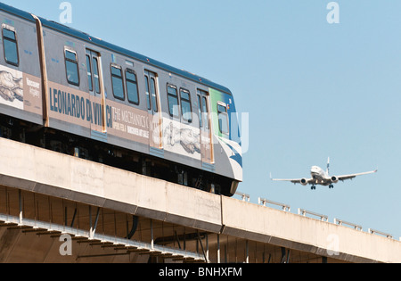 SkyTrain public transit cars and a commercial airliner pass by each other, Vancouver International Airport. - Stock Photo