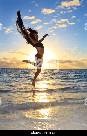 beautiful black female dancer leaping in the air over the ocean at sunrise in the tropics - Stock Photo