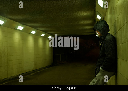 Teenage boy leaning against subway wall at night. - Stock Photo