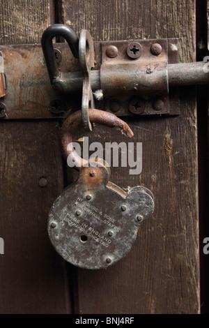 Rusty padlock on rustic wooden door - Stock Photo
