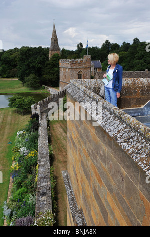 Visitors on the roof of historic Broughton Castle near Banbury in Oxfordshire. overlooking the gatehouse and church - Stock Photo