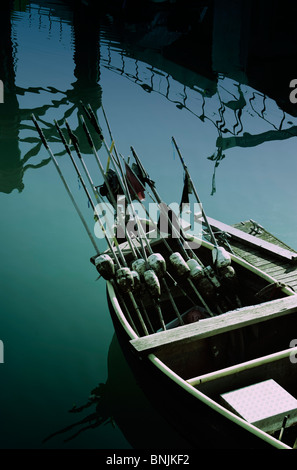 A small fishing boat with marker bouys in a harbour with reflections - Stock Photo