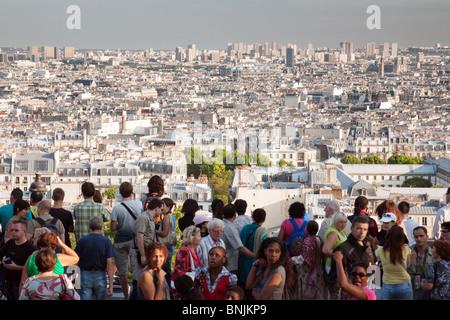 Crowds of  tourists look out at the view over Paris from the Basilique du Sacre Coeur, Montmartre, Paris, France - Stock Photo