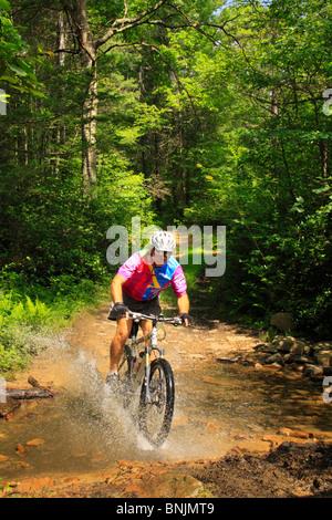 Mountain biker crossing stream in George Washington National Forest near Dayton, Virginia, USA - Stock Photo