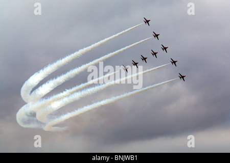 The Red Arrows in T Formation during an air display with white vapour trails showing up clearly against a grey sky - Stock Photo