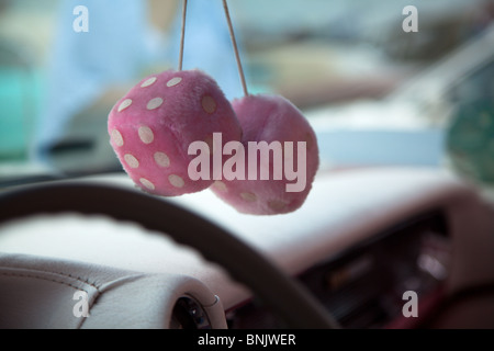 A close up shot of a pair of Pink fluffy furry dice hanging from the rear view mirror in an old car at Fairford, - Stock Photo