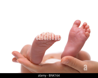 Closeup of newborn baby's feet on a mother's hand. Isolated on white background. - Stock Photo