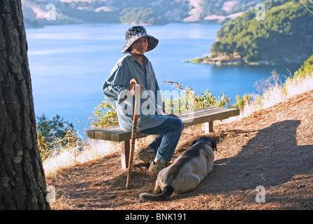 a senior lady rests with her dog overlooking a lake - Stock Photo