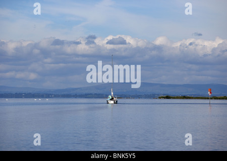 yacht motoring out to set sail on lough neagh northern ireland uk - Stock Photo
