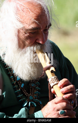 An older man playing a Native American flute - Stock Photo
