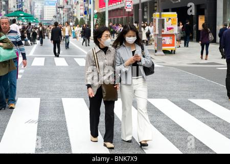 Women wearing protective face masks in Chuo-dori in Ginza 4-chome, Tokyo, Japan - Stock Photo