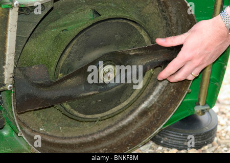 Checking cutting blade on a self-propelled rotary mower - Stock Photo