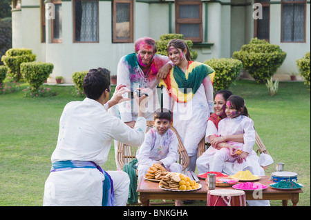 Man filming his family with a video camera on Holi - Stock Photo
