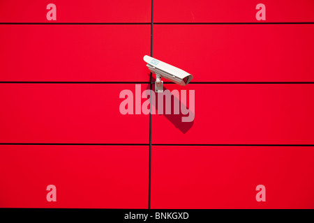 Surveillance camera at a red, modern house front - Stock Photo