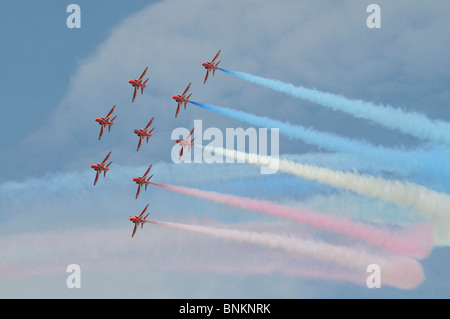 The Red Arrows RAF aerobatic display team flying their Hawk aircraft in formation with red white blue smoke on above - Stock Photo