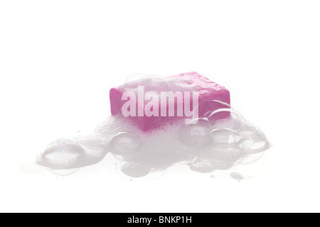 A bar of pink soap with soap bubble isolated on white background - Stock Photo