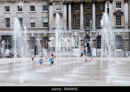 Children playing in the fountains at Somerset House, The Strand, London, England, UK - Stock Photo