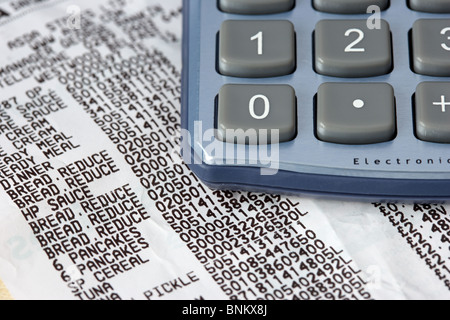 supermarket till receipt showing reduced items and calculator - Stock Photo