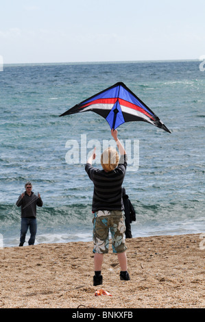 Boy letting go of a small kite with his dad having fun on the beach with the sea behind them - Stock Photo