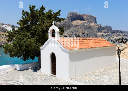 Whitewashed chapel in St Paul's Bay with the Acropolis behind, Lindos, Rhodes, Greece - Stock Photo
