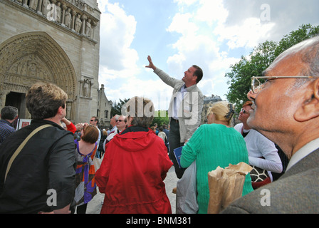crowd of tourists listening to tour guide in front of Notre Dame Paris France - Stock Photo