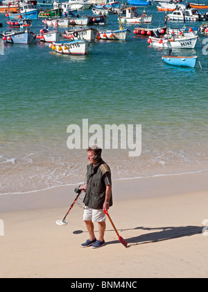 a man using a metal detector on the beach at st.ives in cornwall, uk - Stock Photo