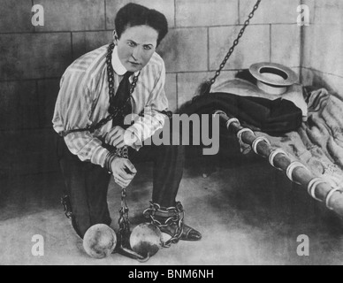 Promotional photo c1898 of magician + escapologist Harry Houdini (1874 - 1926) restrained in chains and locked in - Stock Photo