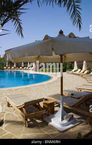 Sun loungers around a swimming pool - Stock Photo