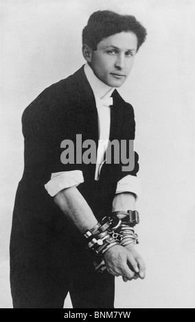 Portrait photo circa 1905 of magician and escape artist Harry Houdini (1874 - 1926) wearing multiple sets of handcuffs. - Stock Photo