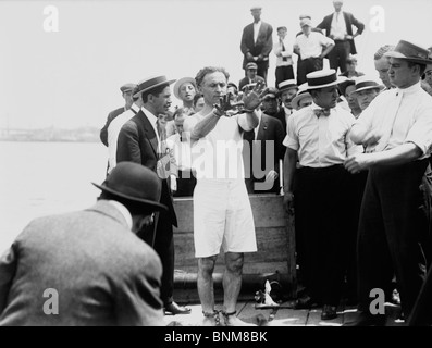 Escapologist Harry Houdini (1874 - 1926) preparing to perform an escape trick - probably his famous 'overboard box - Stock Photo
