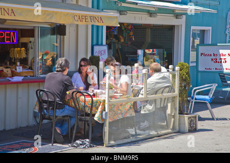 People dining outdoors on Historic Fishermans Wharf shopping and restaurant area in Monterey California - Stock Photo