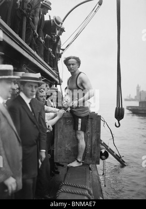 Escapologist Harry Houdini (1874 - 1926) preparing to perform his famous 'overboard box escape' for the first time - Stock Photo