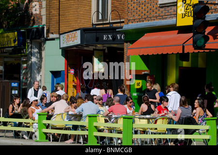 People enjoying the summer on sidewalk terrace Avenue Mont Royal in the heart of the Plateau City of Montreal Canada