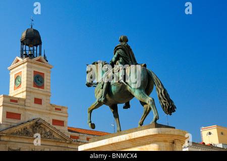 Equestrian statue of King Carlos III and clock tower of Real Casa de Correos, Puerta del Sol, Madrid, Spain - Stock Photo