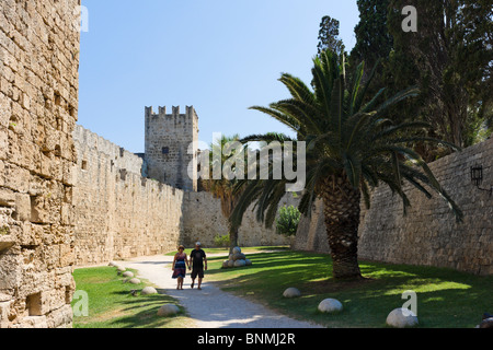 Couple walking along the path in the Medieval moat round the walls of the Old Town, Rhodes Town, Rhodes, Greece - Stock Photo