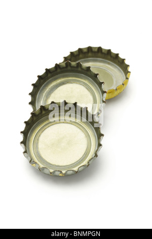 Three bottle caps lying on white background - Stock Photo