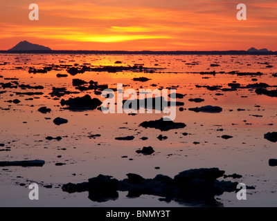 Scattered ice on Turnagain Arm with sun setting behind Mt. Redoubt, Alaska - Stock Photo