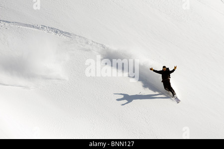 A snowboarder throws up his arms in celebration while snowboarding in Turnagain Pass backcountry, Alaska - Stock Photo