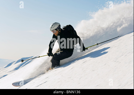 A backcountry skier carving through the powder in Hatcher Pass, Alaska - Stock Photo