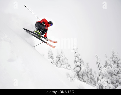 A skier gets a little air while skiing downhill at the Eaglecrest Ski area in Juneau, Alaska - Stock Photo