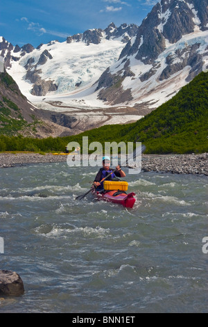 Female kayaker maneuvers down a stream in the Northwestern Fjord of Kenai Fjords National Park, Kenai Peninsula, - Stock Photo