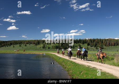 Panorama Guest's Horseback riding Flying A Ranch Guest Ranch Bondurant Wyoming USA forest lake - Stock Photo
