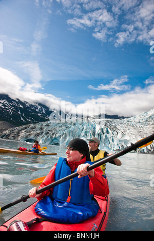 Kayaking couple paddling with Shoup Glacier behind them, Shoup Bay State Marine Park, Alaska - Stock Photo