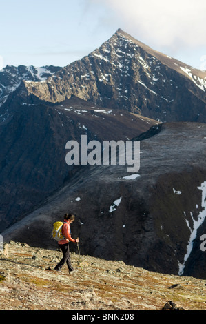 Woman hiking in Chugach State Park with *The Ramp* peak in the background, Alaska - Stock Photo