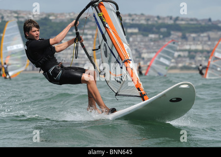 youth windsurfer  heads upwind with hands gripping boom and board flying over the waves, Swansea Bay site of Tidal - Stock Photo
