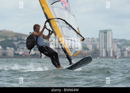 Alli Masters returns to the support boat with backpack.Yellow and white sail. Swansea Tower in the background. Swansea - Stock Photo