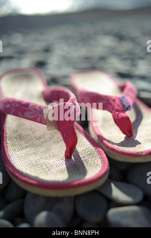 A pair of pink flip flops shoes on a pebble beach, summer UK - Stock Photo